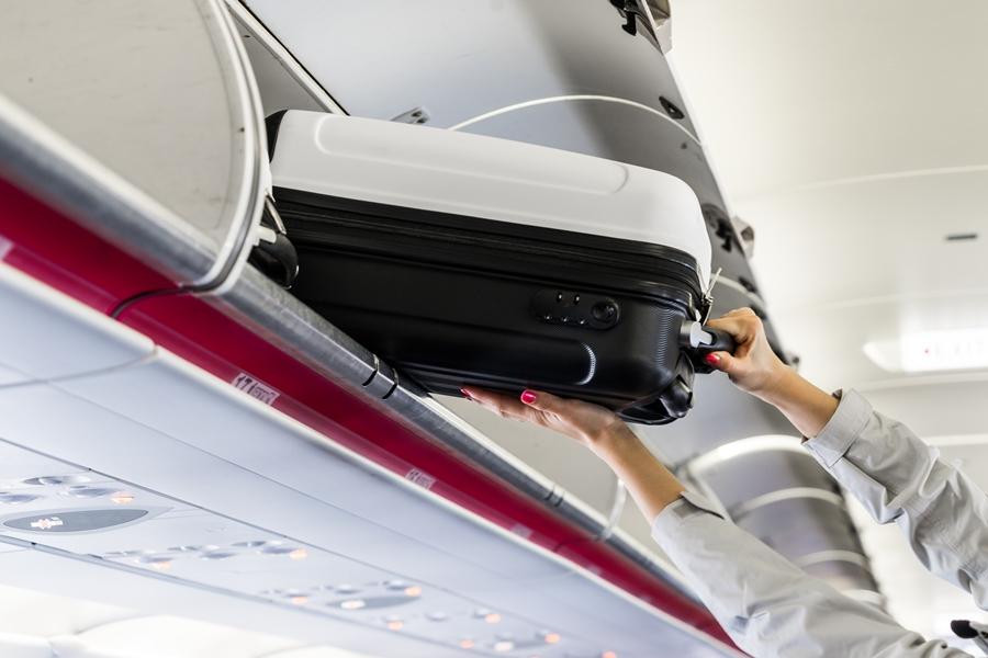 woman-taking-her-hand-luggage-in-airplane-picjumbo-com Bagaglio a mano: cosa mettere quando si viaggia per più giorni